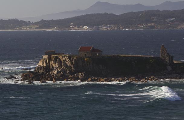 Detalle de la ermita y la torre medieval, al final de una punta que se adentra en el mar.