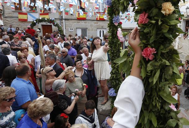 Los fieles se llevan las flores bendecidas del arco frente a la capilla de la Virgen del Carmen.