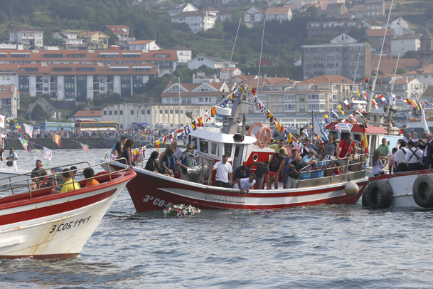 Las embarcaciones se apresuran a cumplir con el ritual alrededor de la corona de flores.
