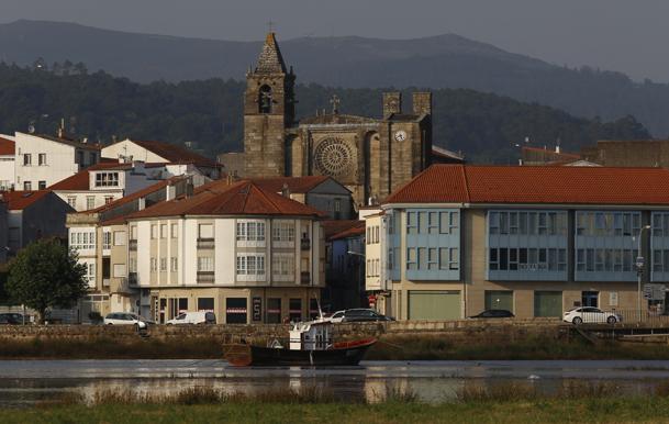 Vista de Noia desde el río, con la iglesia de San Martiño en lo alto.