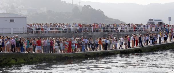 La procesión marítima es contemplada desde los muelles por numerosas personas.