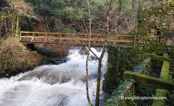 Puente de madera sobre el río Tinto, junto a uno de los molinos y una canalización del agua.